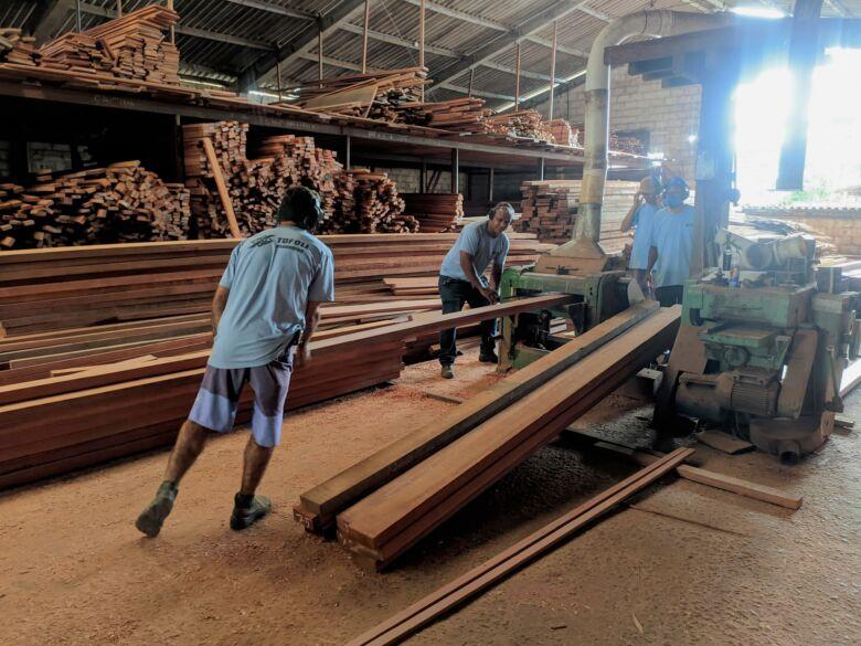 Funcionários na Tofoli Madeiras realizam corte de peças.