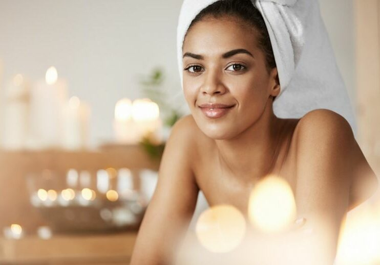 Portrait of beautiful african girl with towel on head smiling looking at camera resting in spa salon.