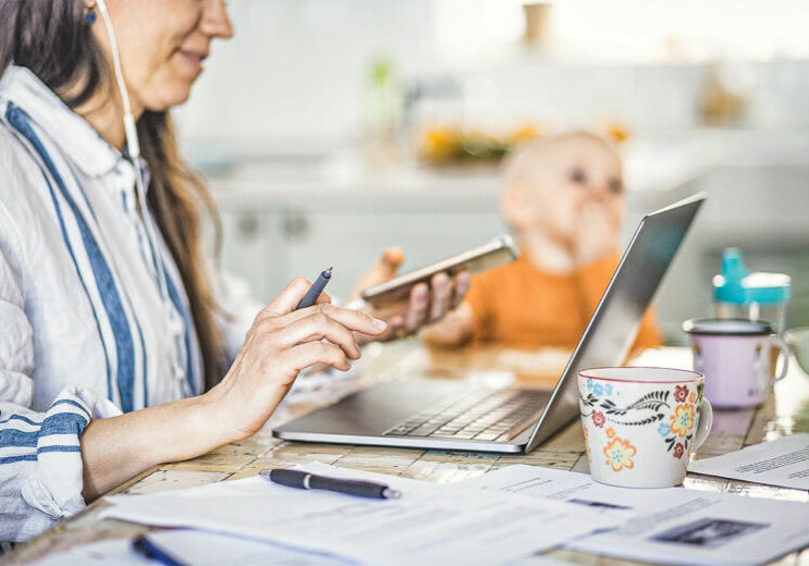 Midsection of working mother using technologies while daughter sitting in background at dining table