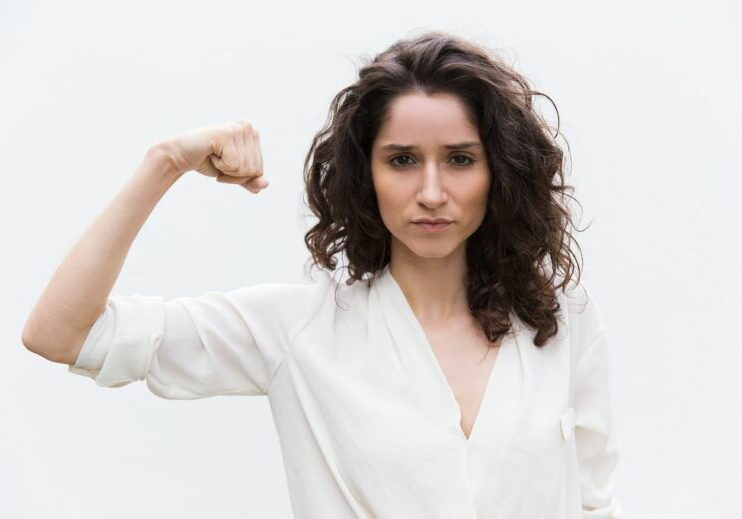 Confident serious woman flexing bicep, showing hand muscle. Wavy haired young woman in casual shirt standing isolated over white background. Girl power or feminism concept