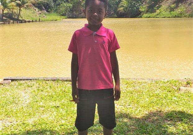 Menino Luiz Guilherme, de apenas 8 anos, vestindo bermuda preta e camiseta rosa em frente a uma lagoa