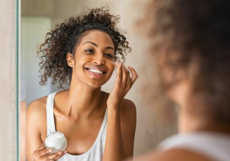 Black woman take care of her beautiful skin. Young african woman applying moisturizer on her face while standing in front of the mirror. Smiling black natural girl holding little jar of skin lotion in bathroom for beauty treatment routine.