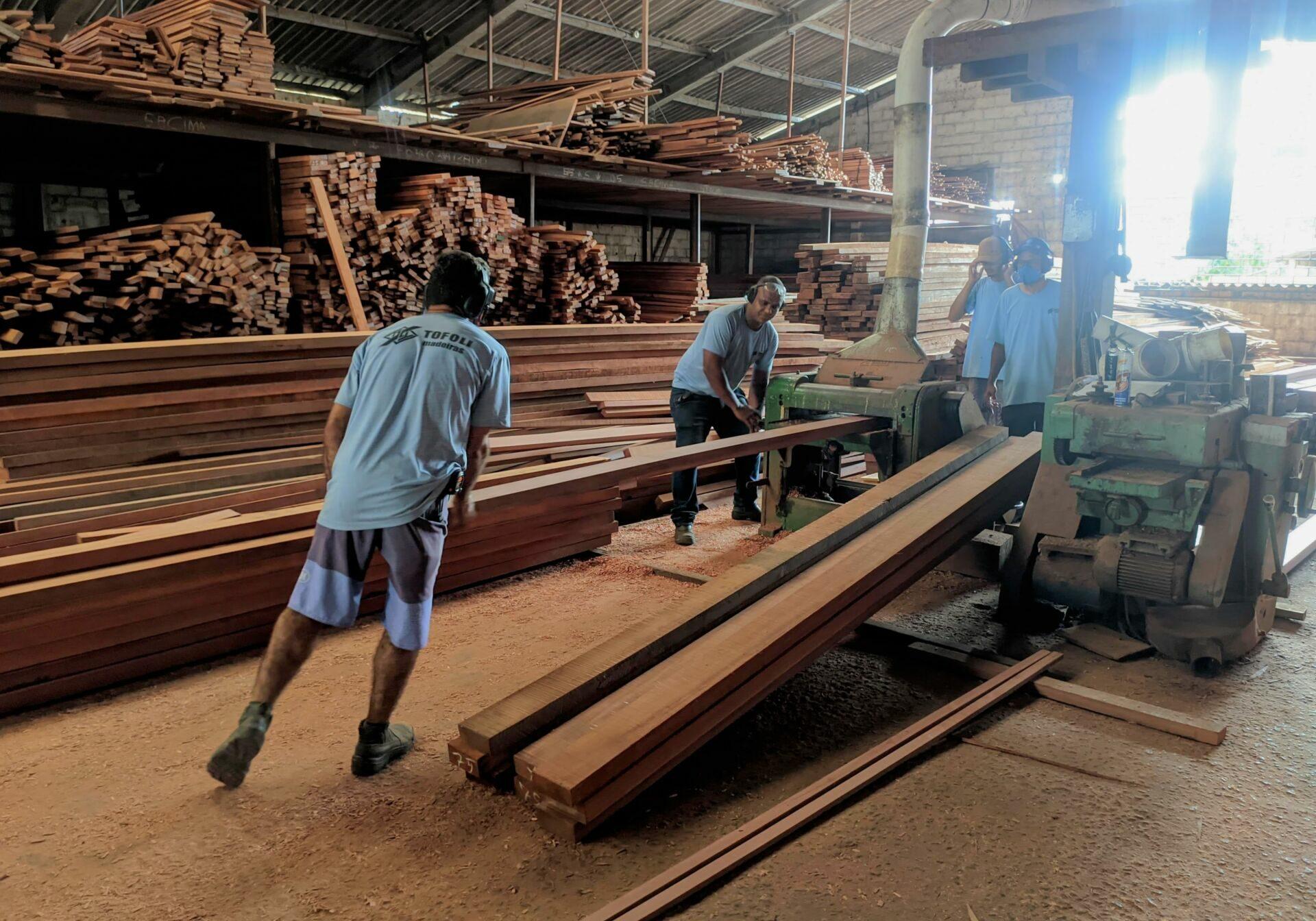 Funcionários da Tofoli realizam corte de peça em madeira.